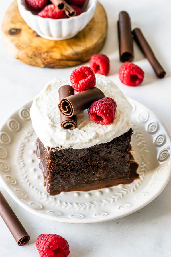 chocolate tres leches topped with whipped cream chocolate curls and raspberries