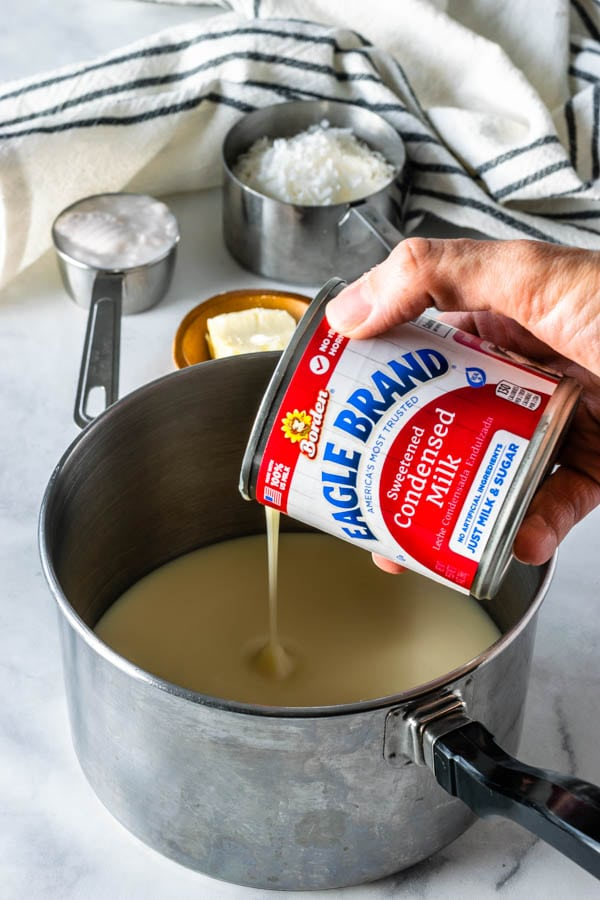 pouring condensed milk in a small saucepan