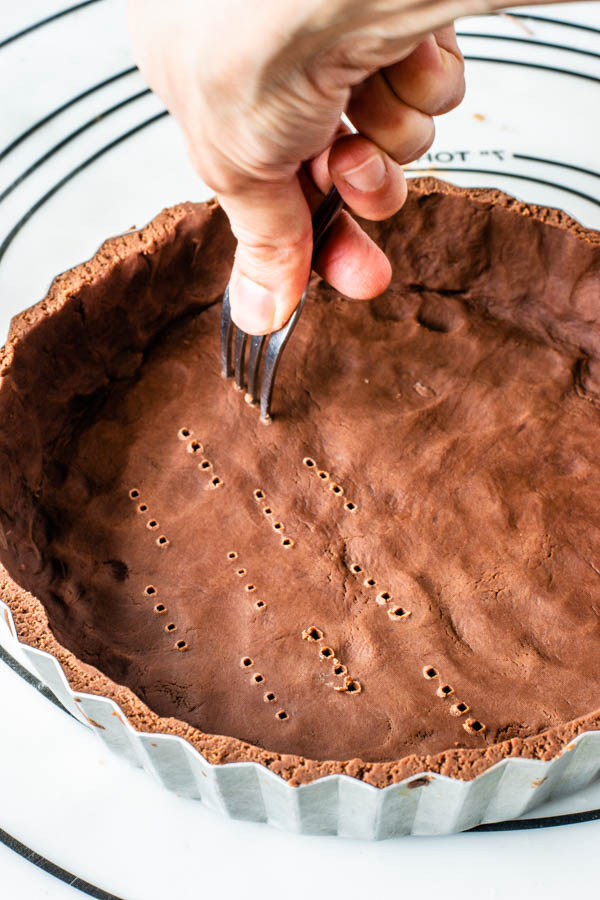 poking the bottom of a chocolate tart dough with a fork