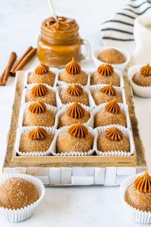 dulce de leche brigadeiro coated in cinnamon and sugar with dulce de leche piped on top