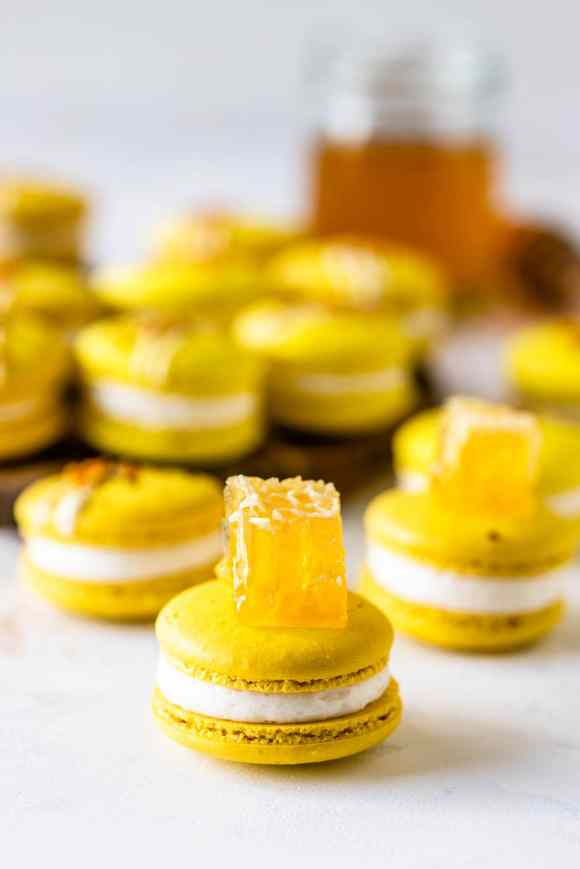 yellow Macarons topped with a piece of honey comb on a wooden board with a jar of honey on the back