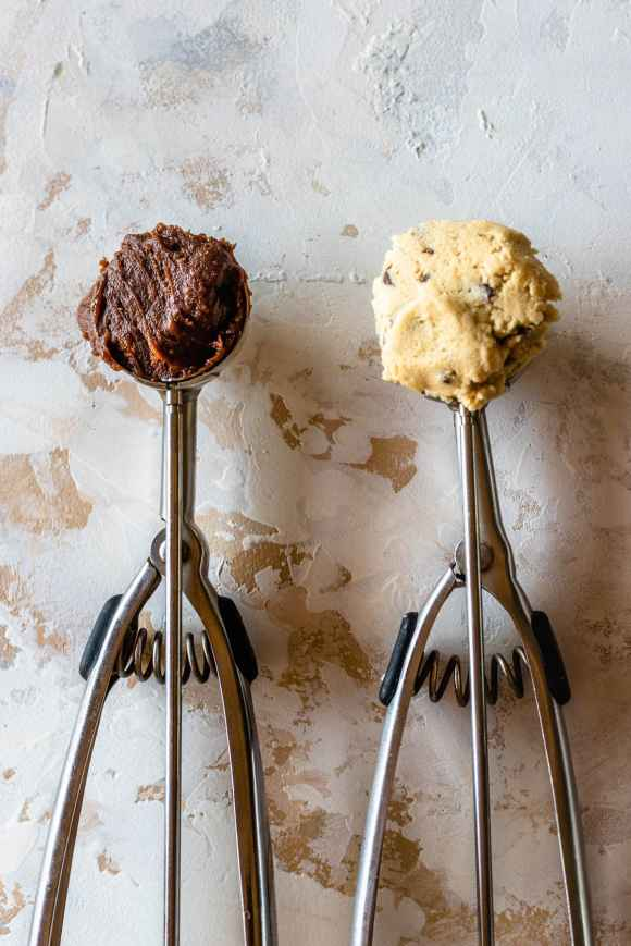 two cookie scoops one with brownie batter and the other with chocolate chip cookie dough