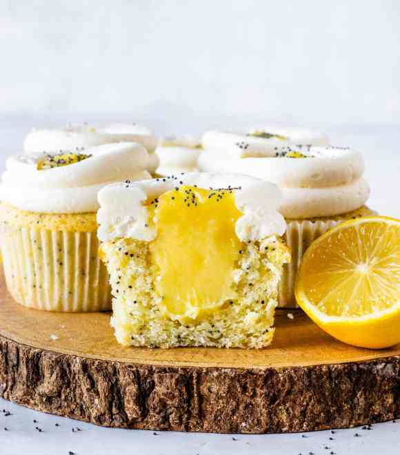 lemon poppy seed cupcakes filled with lemon curd cut in half to show the filling of the curd