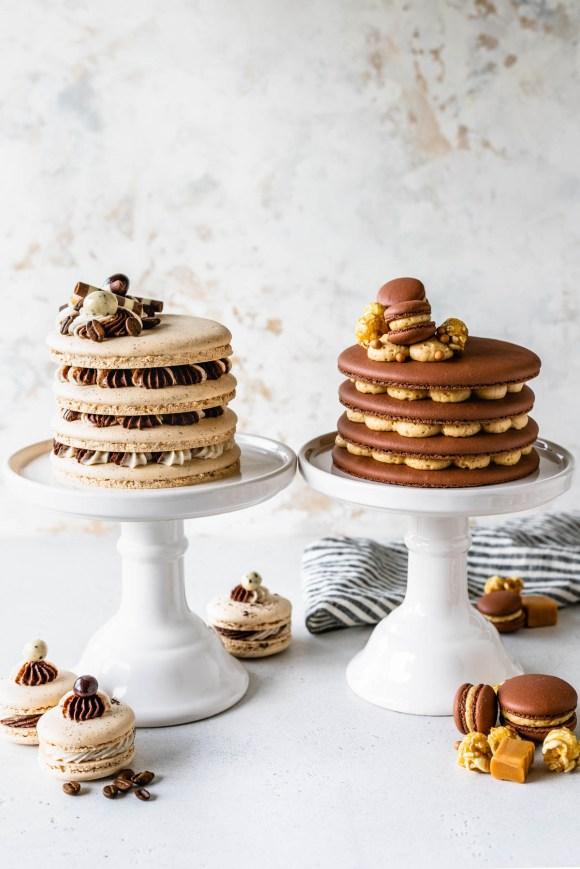 Caramel Macaron Cake layers of chocolate macaron shells filled with caramel buttercream topped with mini macarons, caramel popcorn, next to coffee macaron cake, topped with coffee beans covered in chocolate.