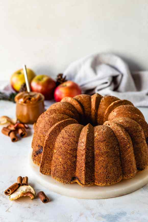 apple bundt cake, with apples on the background.