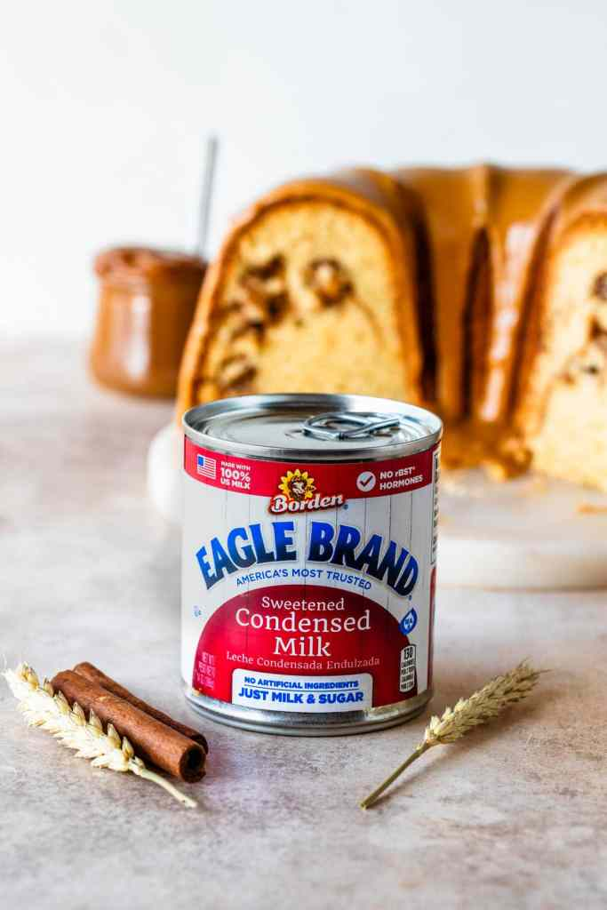 can of eagle brand® sweetened condensed milk in front of a cake.