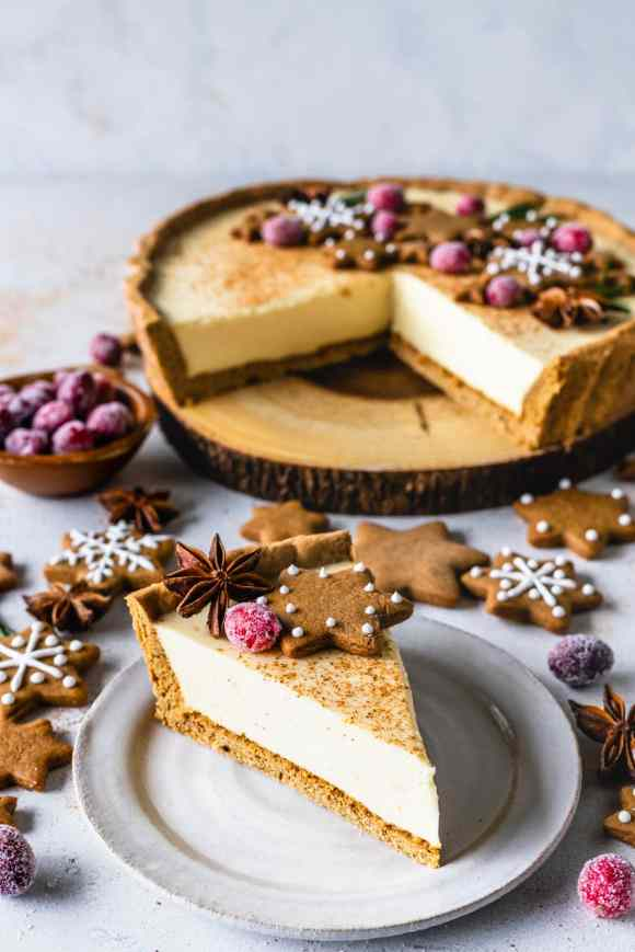 slice of christmas pie filled with eggnog topped with gingerbread cookies and sugared cranberries.