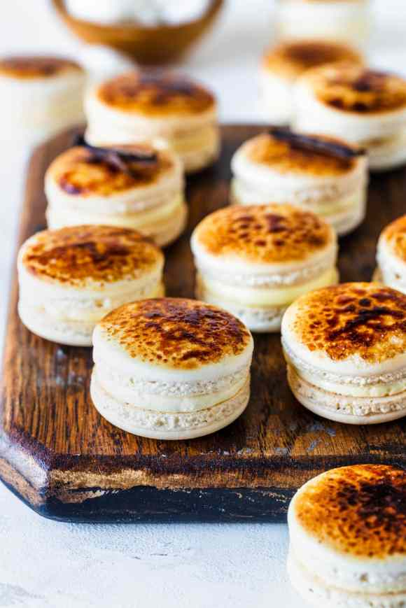macarons with a bruleed top caramelized, on top of a wooden board.