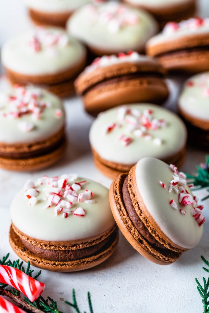 macarons filled with peppermint dark chocolate ganache and peppermint white chocolate ganache, topped with melted white chocolate and crushed candy canes, displayed on a plate.