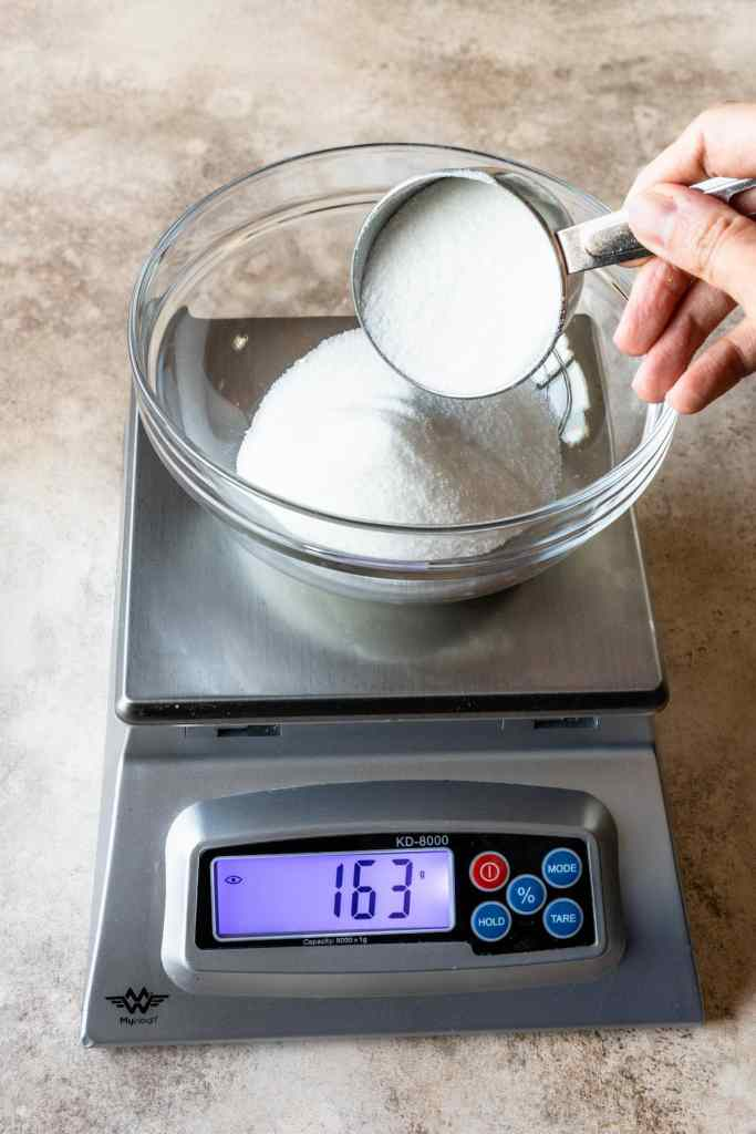 adding sugar to a bowl on top of a scale.