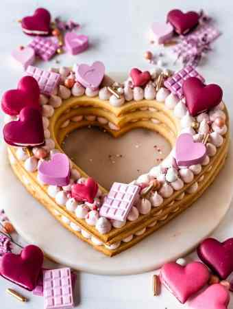 cookie cake shaped like a heart decorated with buttercream, macaron hearts, pink chocolate hearts.