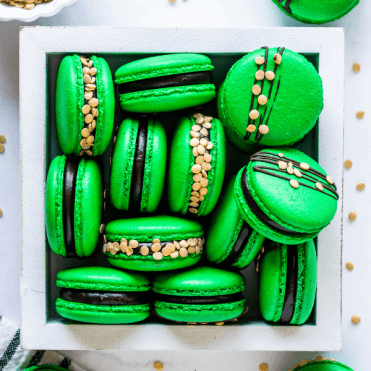 green macarons topped with gold sprinkles.
