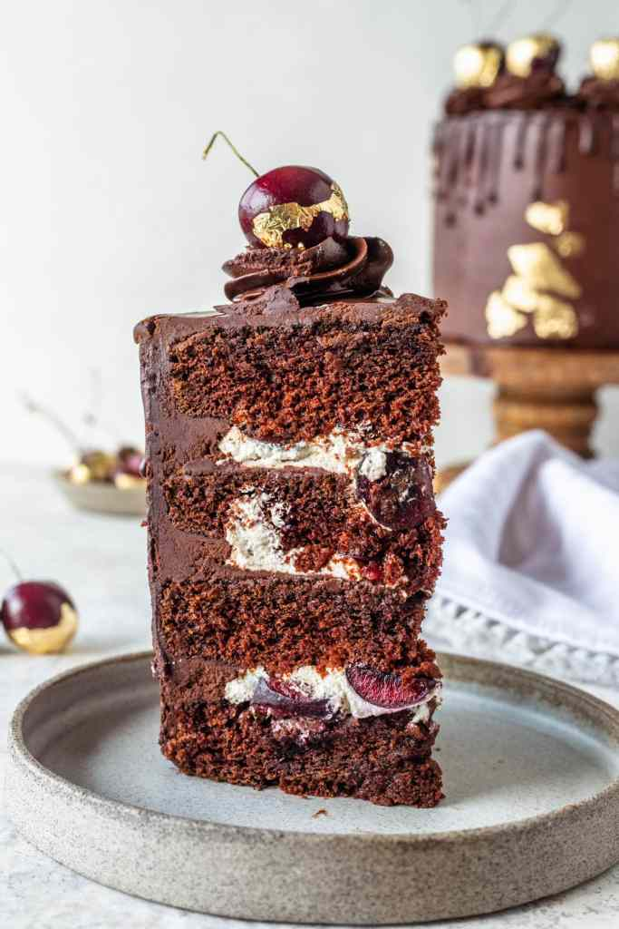 slice of Chocolate Cherry Cake topped with chocolate pudding frosting and gold cherries.