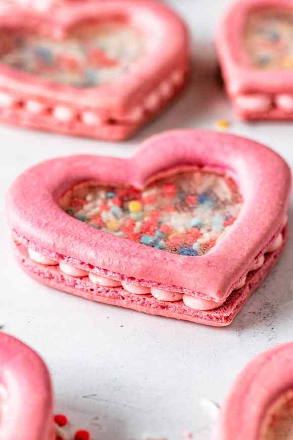 heart shaker macarons filled with sprinkles and they have a transparent middle.