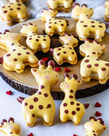 Giraffe Macarons with heart sprinkles around, and a mama and a baby giraffe.