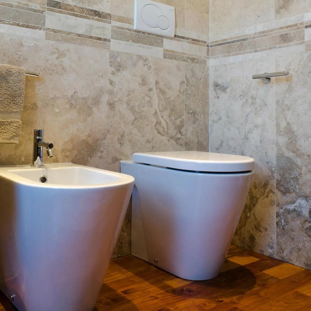 Bagno con rivestimento in travertino e pavimento in legno