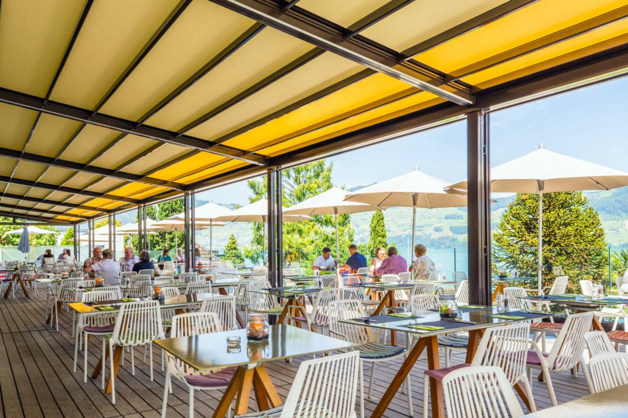 Die Gastro- Markise, RIVERA P5000, ist die Nummer 1 auf Ihrer privaten Terrasse oder für große Flächen in der Außengastronomie. Sie ist entwickelt für besondere Größen. Manchmal darf es eben etwas mehr sein. Besonders große Terrassen bieten viel Komfort, deshalb sind die Anforderungen an den Schutz vor Sonne, Wind und Regen auch besonders hoch. Das multifunktionelle Terrassendach RIVERA P5000 bietet im Standard bis zu 105 m² zuverlässigen Sonnenschutz und Regenschutz. Mit der neuen RIVERA P5000 kreieren Sie auf jeder Terrasse großzügigen Freiraum im eleganten Design. Die integrierte Faltmarkise spendet bei Sonnenschein kühlen Schatten und schützt vor schädlicher UV- Strahlung. Wenn es regnet, leitet das straff gespannte und wasserdichte RESISTANT- Polyestergewebe das Wasser kontrolliert zum Ablaufsystem im Frontbereich. Erweitern Sie den Open-Air- Genuss mit komfortablen Optionen. Die stromsparende LED- Beleuchtung zaubert nachts ein stimmungsvolles Ambiente auf Ihre Terrasse. Mit den variablen Schiebeverglasungen profitieren Sie von zusätzlichem Schutz gegen Wind und Wetter und verlängern dadurch Ihre Freiluft-Saison - Panoramaausblick inklusive. Auf Wunsch sorgt die harmonisch integrierte, dimmbare LED- Beleuchtung für Terrassengenuß bis tief in die Nacht hinein. Infrarotstrahler sorgen für wohlige Wärme von der ersten Sekunde an. Die Bedienung per Funk ist ebenso möglich. Exklusiver kann eine Terrasse nicht vor zu viel Sonne, Wind und Regen geschützt werden! Facts & Figures Großflächiges, maßgefertigtes Terrassendach Elegante Sonnen- und Regenschutzlösung Flexibel einsetzbar für Privat und Gastronomie Regendichte Faltmarkise mit robustem, schmutzabweisendem Polyestergewebe, Brandschutzklasse B1 Integrierter Wasserablauf Dachneigung von 8° bis 25° Korrosionsbeständige Aluminiumkonstuktion Serienmäßig mit Elektroantrieb Komfortabel erweiterbar durch: Integrierte, dimmbare LED- Beleuchtung Schiebbare Seiten- und Frontverglasung Aluminium Systemboden,Klaiber Markise,