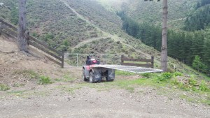 Using the 4 wheeler to get the gate over to the fence line in the distance