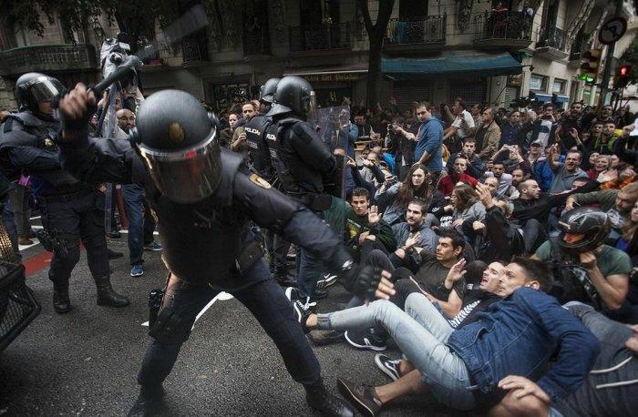 Policía nacional golpeando a manifestantes sentados en el suelo durante la jornada del 1O en Cataluña