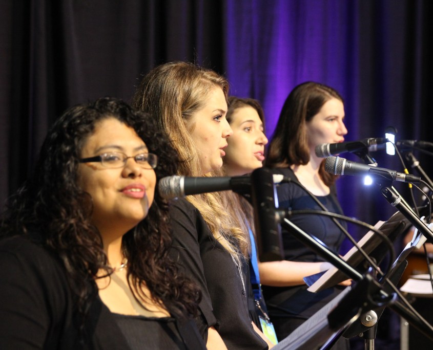 Young women lead the conference in joyful song