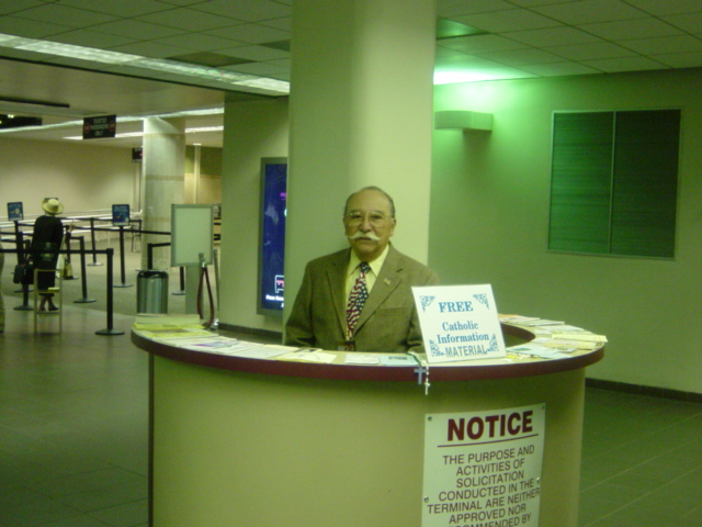 Manny Marin stands behind a round booth at San Antonio International Airport