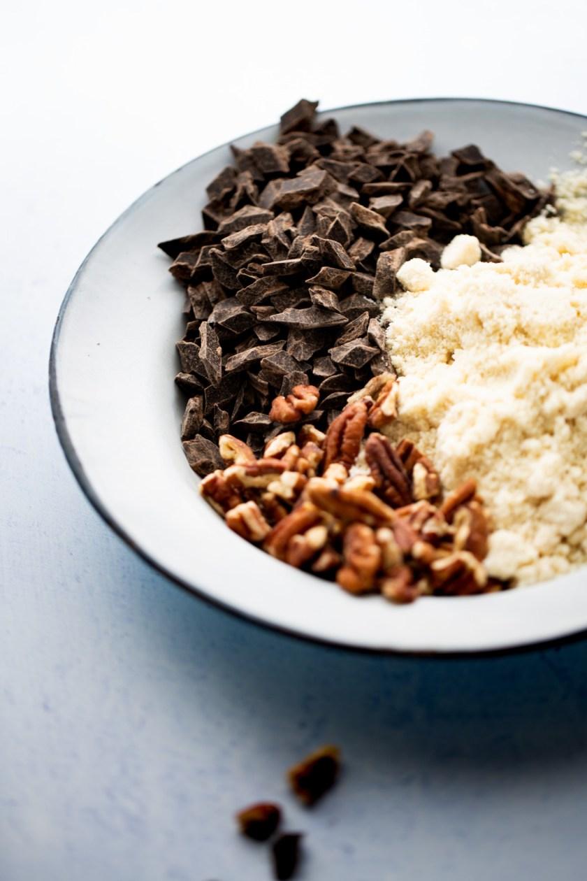 plato con nuez, chocolate y harina de almendra para hacer brownies veganos
