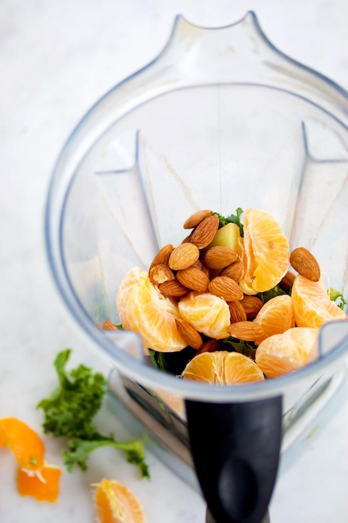 Mandarina, kale y almendras para hacer smoothie verde en el vaso de la licuadora.
