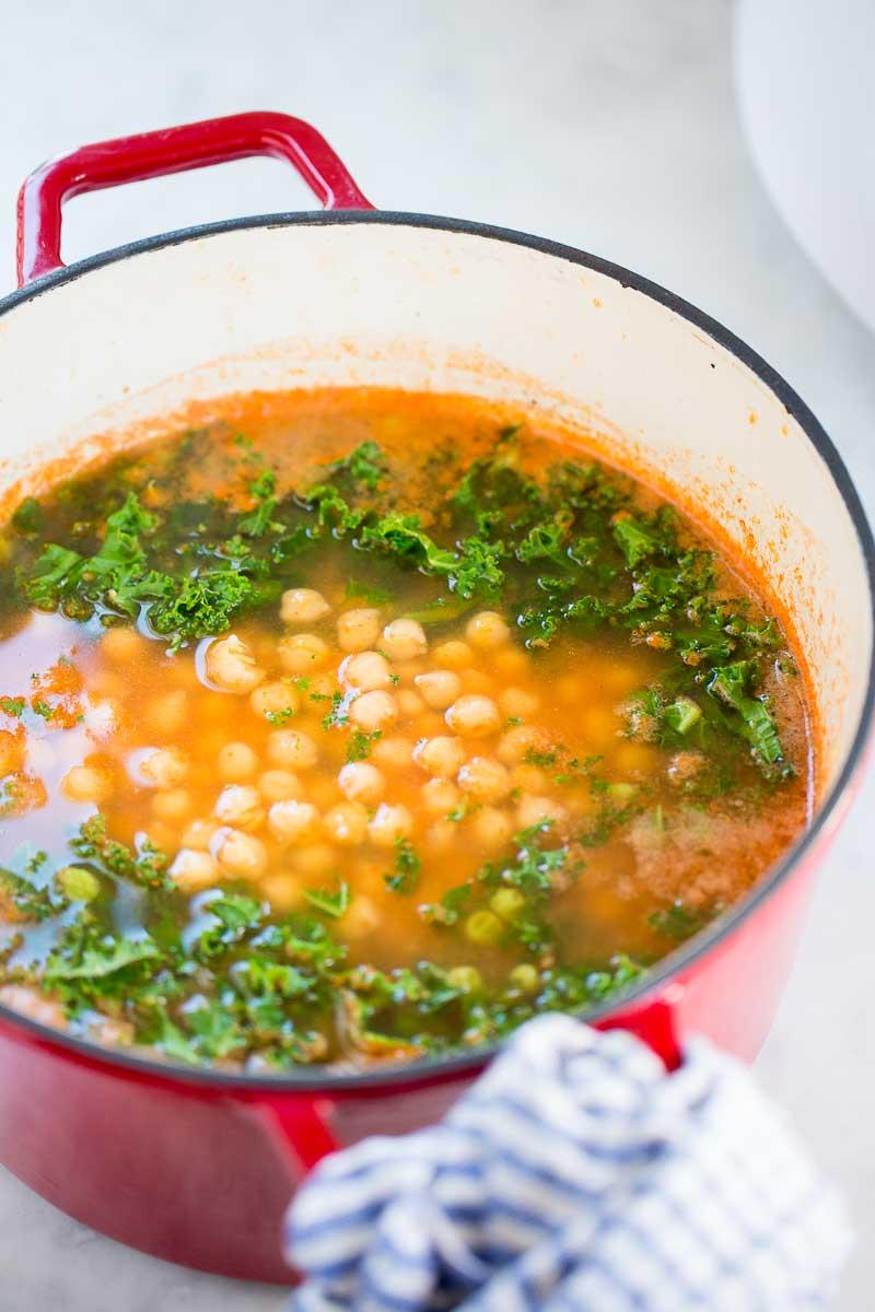 Olla dr hierro forjado con sopa de pasta con garbanzos y hojas verdes