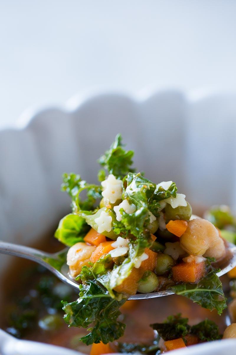 Una cucharad de sopa de verduras con garbanzo y estrellitas de pasta