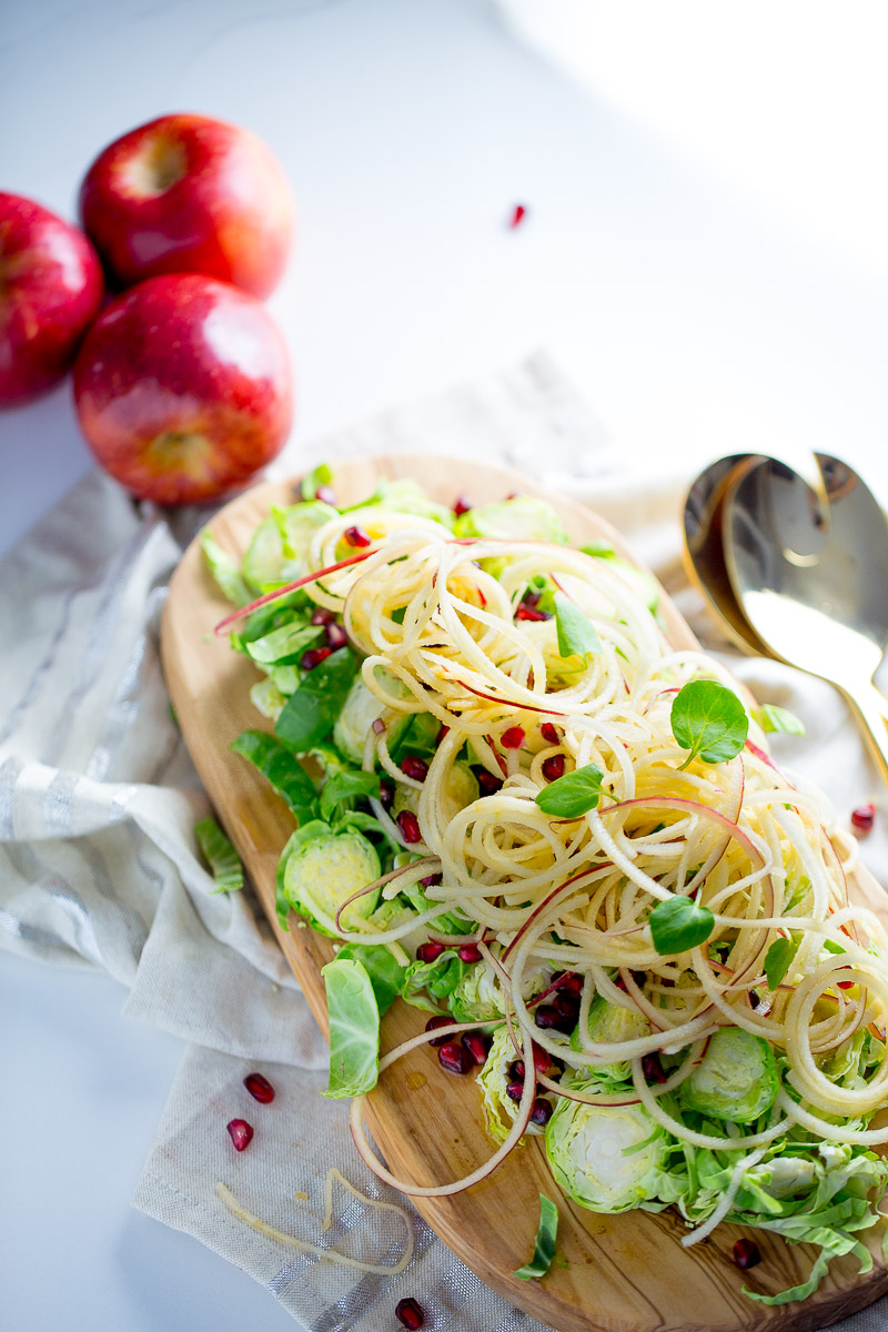 Apple salad with brussels sprouts, pomegranate seeds, and maple- balsamic vinegar dressing