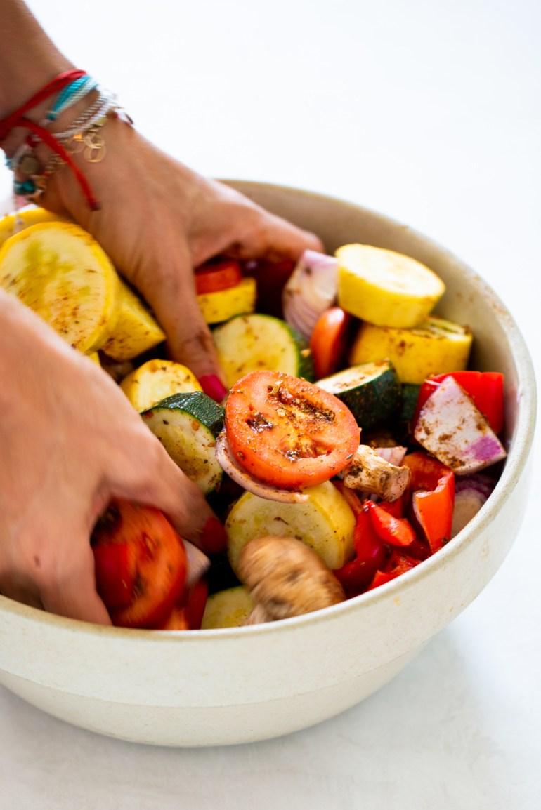 mezclando verduras con especies y aceite