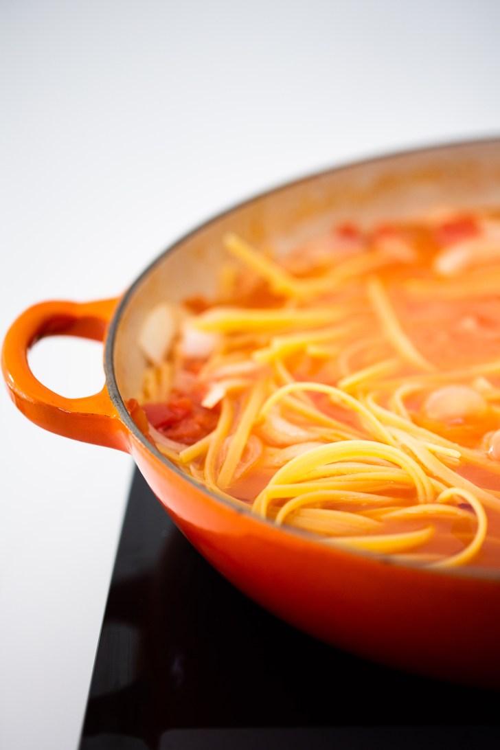 Pasta en la olla con salsa.