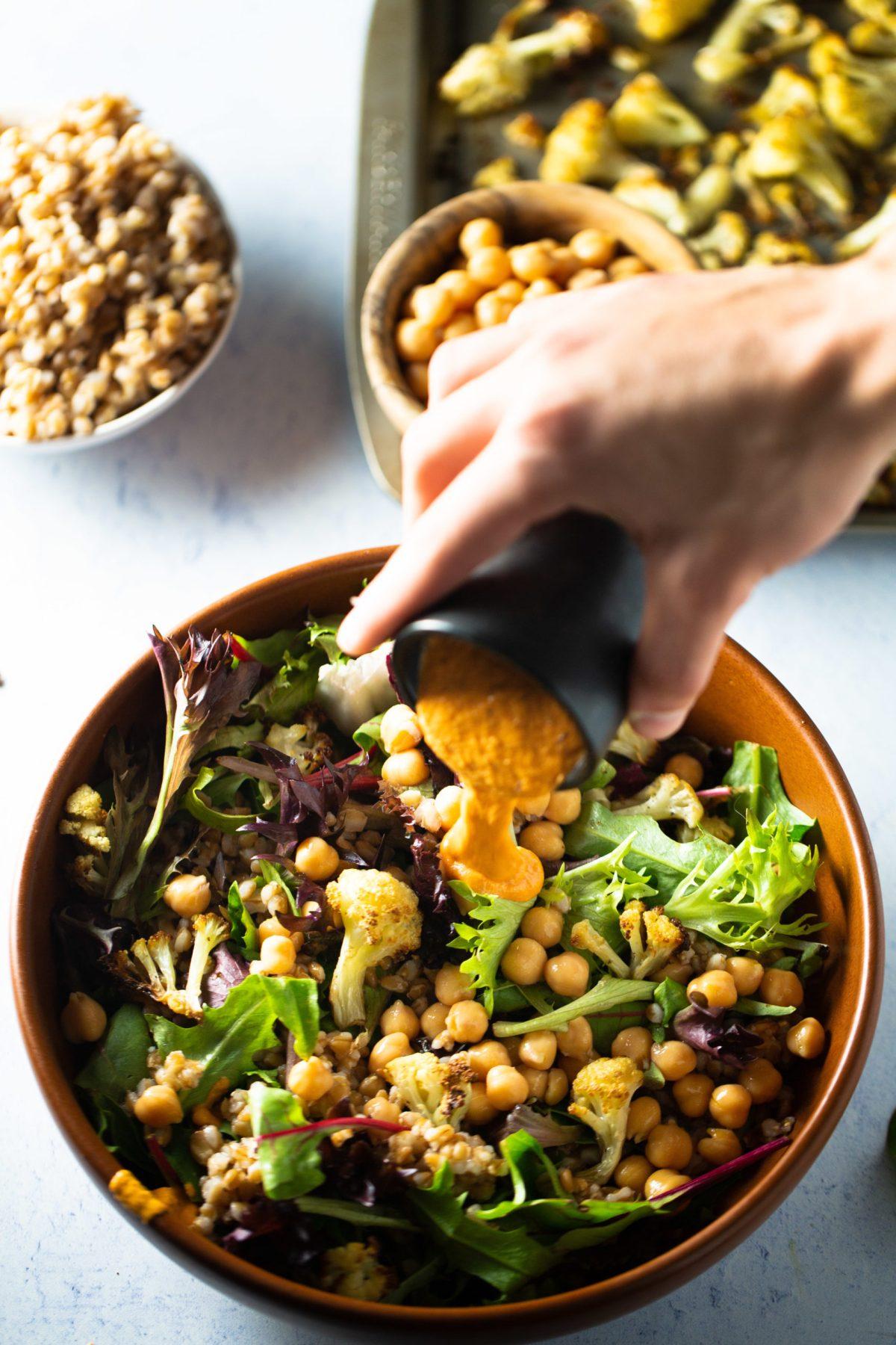 Romesco cayendo en ensalada de farro con coliflor, garbanzos y hojas verdes.