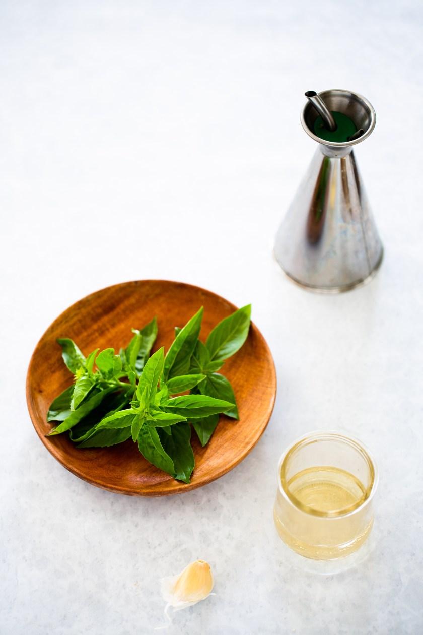 Ingredientes para hacer aderezo, aceite de oliva, ajo, vinagre y albahaca.