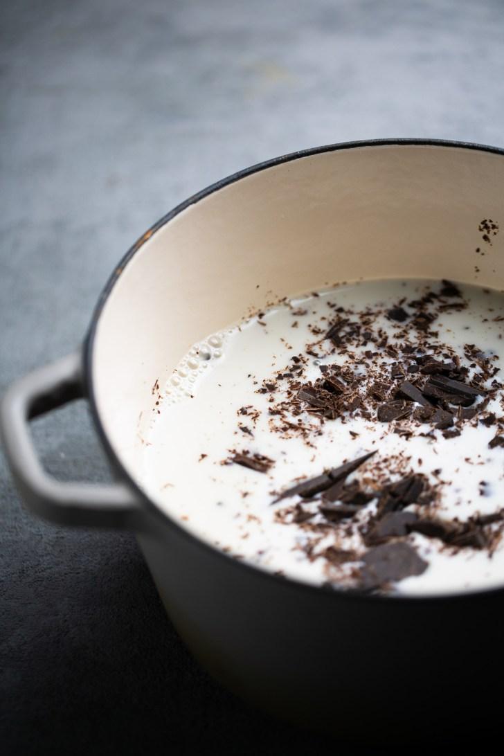 Olla con leche y pedazos de chocolate caliente