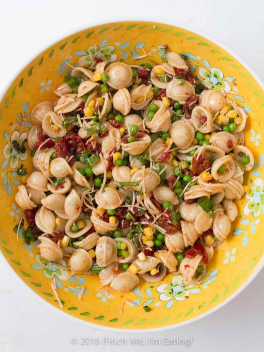 Full of fresh basil and veggies, this lightly dressed sun-dried tomato pasta salad is a refreshing and flavorful side dish for sandwiches, a potluck, or a light lunch! Copycat recipe from Beyond Bread in Tucson, AZ.   www.pinchmeimeating.com