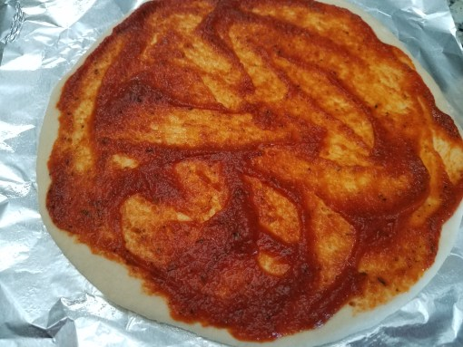 An 11 inch pizza on foil with sauce added on top