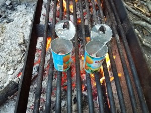 Two juice cans with bacon on a cooking grate over the fire