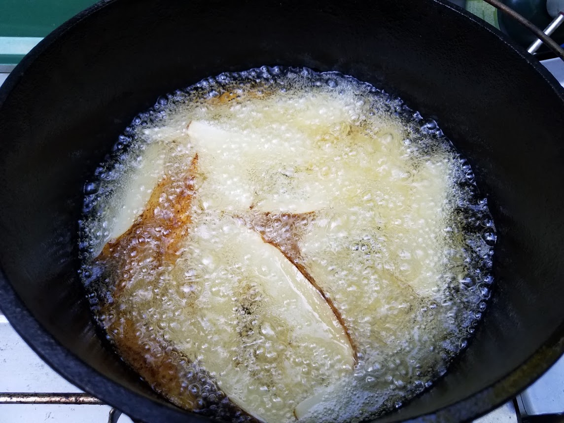 potatoes frying beautifully in a dutch oven on a camp stove
