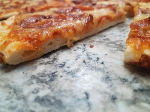 A sliced grilled pizza, with one slice pulled out to reveal the crust