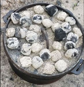 A dutch oven with several coals on top