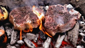 Two seasoned steaks cooking directly on coals