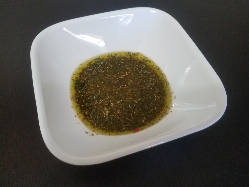 Italian chicken marinade in a white bowl on a black table