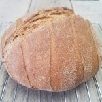 whole wheat dutch oven bread cooling on wire rack