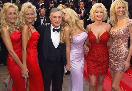 "CANNES, FRANCE:  Playboy magazine president Hugh Hefner (C) poses with playmates 14 May 1999 on the steps of the Palais des Festivals before the screening of their movie ""Entrapment"" in selection for the 52nd Cannes Film Festival. (ELECTRONIC IMAGE) (Photo credit should read PASCAL GUYOT/AFP/Getty Images)"