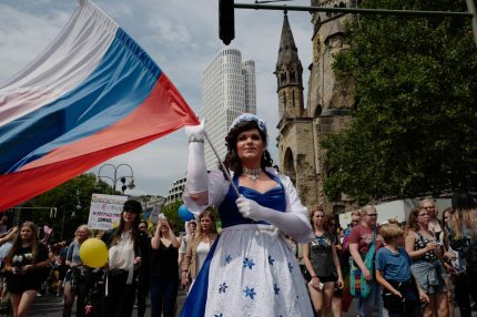 A participant from Russia waves a Russian flag during Berlin's annual Christopher Street Day (CSD) gay pride parade on July 22, 2017. Gays and lesbians all around the World are celebrating the Christopher Street Day (CSD) gay and lesbian pride parade. / AFP PHOTO / John MACDOUGALL        (Photo credit should read JOHN MACDOUGALL/AFP/Getty Images)