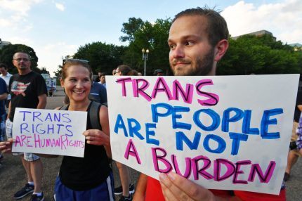"Protesters gather in front of the White House on July 26, 2017, in Washington, DC. Trump announced on July 26 that transgender people may not serve ""in any capacity"" in the US military, citing the ""tremendous medical costs and disruption"" their presence would cause. / AFP PHOTO / PAUL J. RICHARDS (Photo credit should read PAUL J. RICHARDS/AFP/Getty Images)"