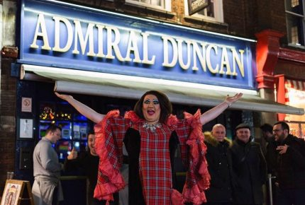 Men and drag queen standing outside the Admiral Duncan London gay bar