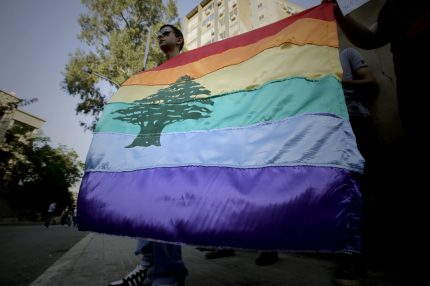 """A gay pride flag bearing the cedar tree in the middle of it is carried by human rights activists during an anti-homophobia rally in Beirut on April 30, 2013. Lebanese homosexuals, human rights activists and members from the NGO Helem (the Arabic acronym of """"Lebanese Protection for Lesbians, Gays, Bisexuals and Transgenders"""") rallied to condemn the arrest on the weekend of three gay men and one transgender civilian in the town of Dekwaneh east of Beirut at a nightclub who were allegedly verbally and sexually harassed at the municipality headquarters. AFP PHOTO/JOSEPH EID / AFP PHOTO / Joseph EID (Photo credit should read JOSEPH EID/AFP/Getty Images)"""