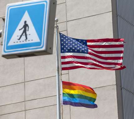 A Pride flag is raised next to the US flag.